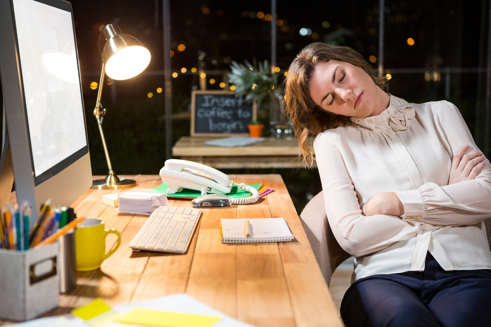 Tired businesswoman sleeping on chair in the office